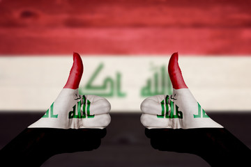 Iraq flag painted on female hands thumbs up