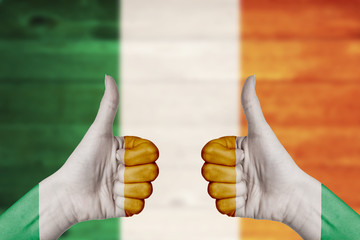 Ireland flag painted on female hands thumbs up