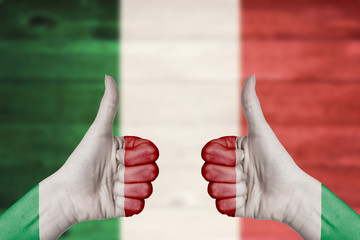 Italy flag painted on female hands thumbs up