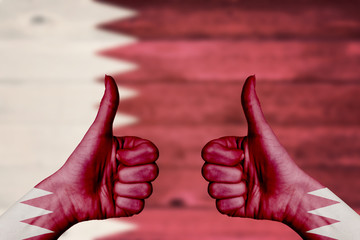 Qatar flag painted on female hands thumbs up