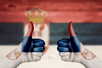 Serbia flag painted on female hands thumbs up