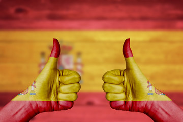 Spain flag painted on female hands thumbs up
