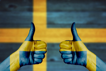 Sweden flag painted on female hands thumbs up