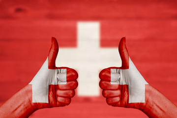 Switzerland flag painted on female hands thumbs up