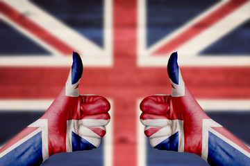 United Kingdom flag painted on female hands thumbs up