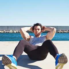 Handsome athlete doing abdominal sport exercises