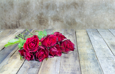 Fresh red rose on wooden background.