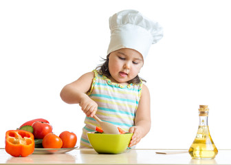 kid girl helping at kitchen with salad making