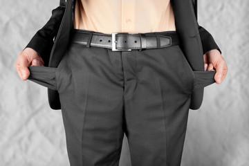 bankrupt  man showing empty pockets