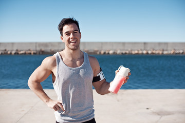 Handsome smiling athlete with protein cocktail