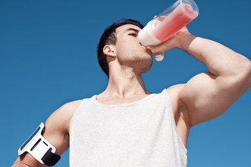Young and handsome athlete drinking protein cocktail