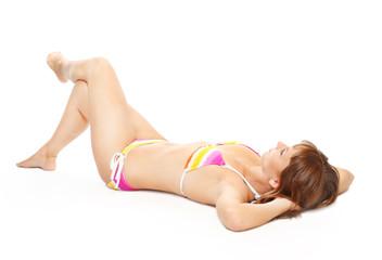 Slim woman dressed in bikini tanning on the beach.