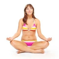 Slim woman dressed in bikini sitting in yoga lotus position.