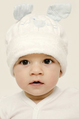 Innocent baby wearing a white bunny hat looking adorable.