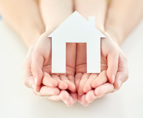 close up of woman and girl hands with paper house