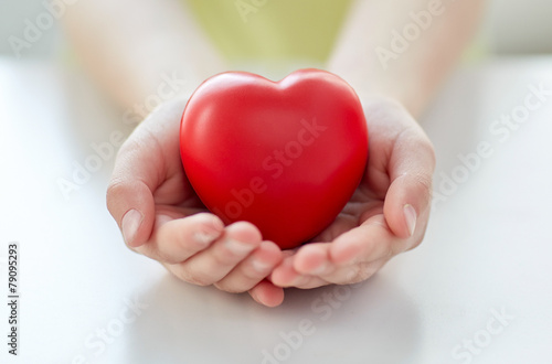 Leinwandbild Motiv close up of child hands holding red heart