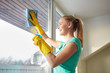 happy woman in gloves cleaning window with rag
