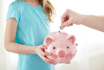 close up of girl with piggy bank putting coin