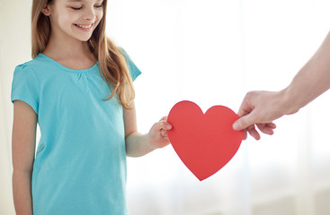 close up of girl and male hand holding red heart