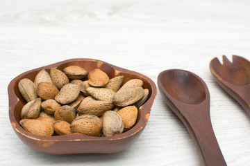 almonds in a bowl and wooden utensils