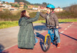 Mother and son giving five by success riding bicycle - 79097433