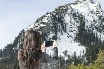 woman on the hill, take a photo with smartphone