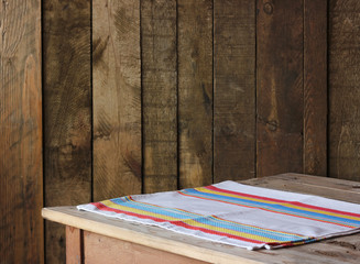 пустой деревянный стол  с полотенцем на фоне стены из досок