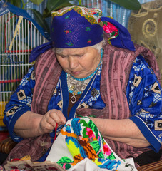 old lady sits by her cross-stitch embroidery