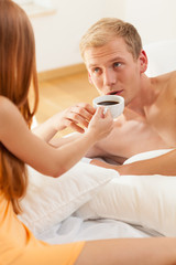 Woman giving coffee to a man in bed