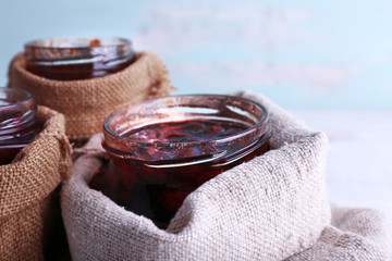 Homemade jars of fruits jam in burlap pouches