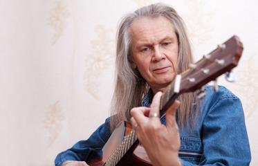 middle-aged man playing guitar closeup
