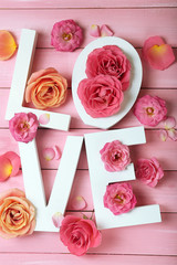 Beautiful roses with word LOVE on pink wooden planks background