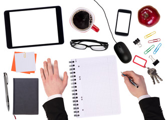 Office desktop with various objects and a businessman working