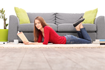 Young woman lying on the floor and reading a book