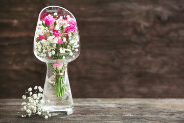 Beautiful bouquet in glass vase on rustic wooden background