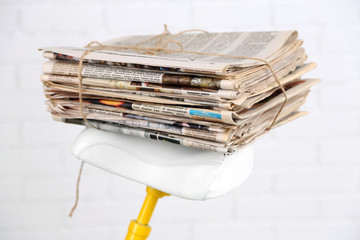 Vintage yellow bicycle with newspaper, on white wall background