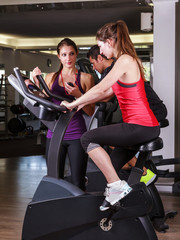 Woman doing fitness with an exercise bike and a coach