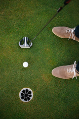 Feet of male golf player putting at green