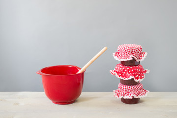 Glass pots jam and red bowl