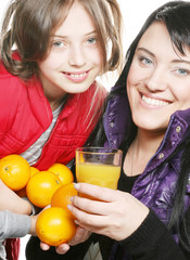 child with mother holding oranges and juice