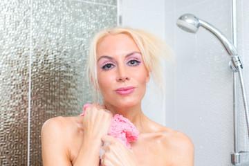 Blonde Frau unter der Dusche