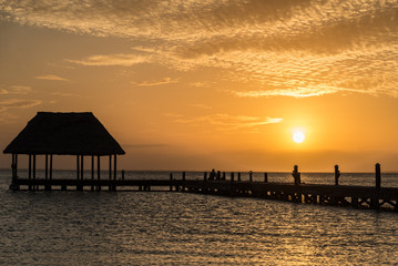 Couple in love at a wooden pier palapa enjoying Sunset at Holbox