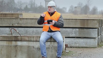 Engineer with tablet PC sitting on the concrete panels
