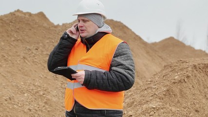 Civil engineer talking on cell phone at a pile of sand