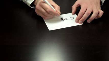 Hands writing the word contract
