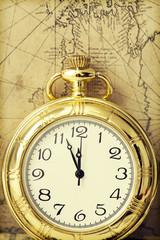 Old pocket watch over vintage map
