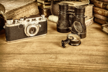 Sepia styled image of camera with compass and books