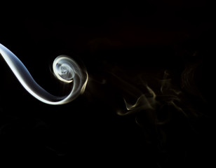 The smoke from the incense sticks on a black background