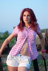 Outdoor shoot of redhair, wood hedge behind her
