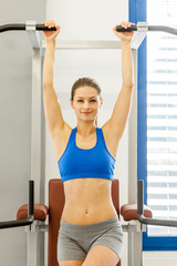 attractive smiling woman is doing exercises for her abs